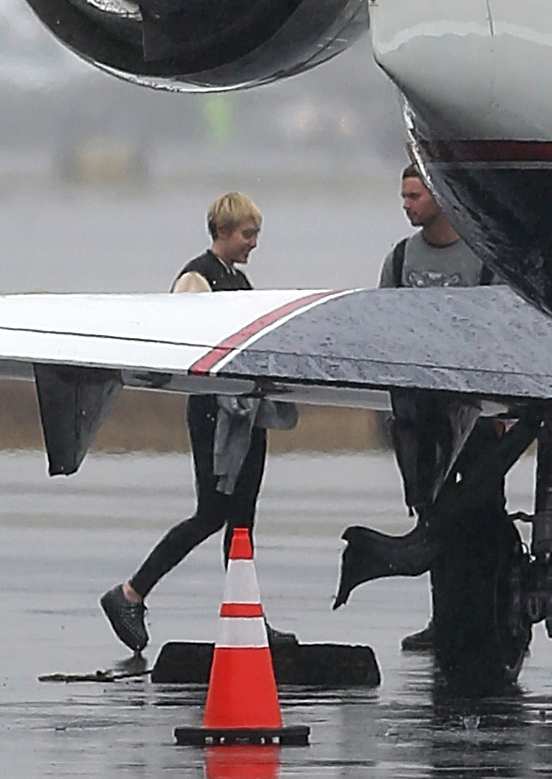 Miley Cyrus jets out of rainy LA with her new beau Patrick Schwarzenegger